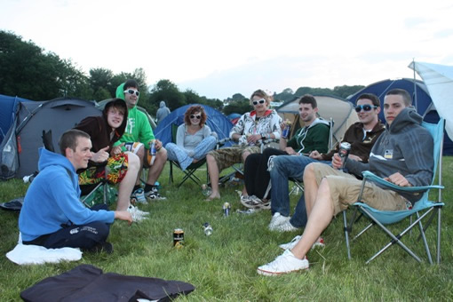 Friends in the campsite enjoy an evening of relaxation prior to the festival arena opening